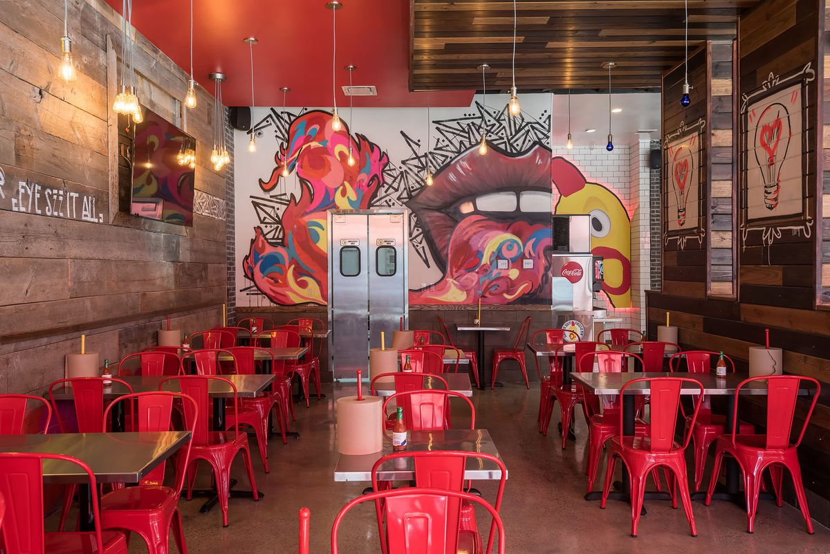 Graffiti wraps the walls of a red restaurant interior.