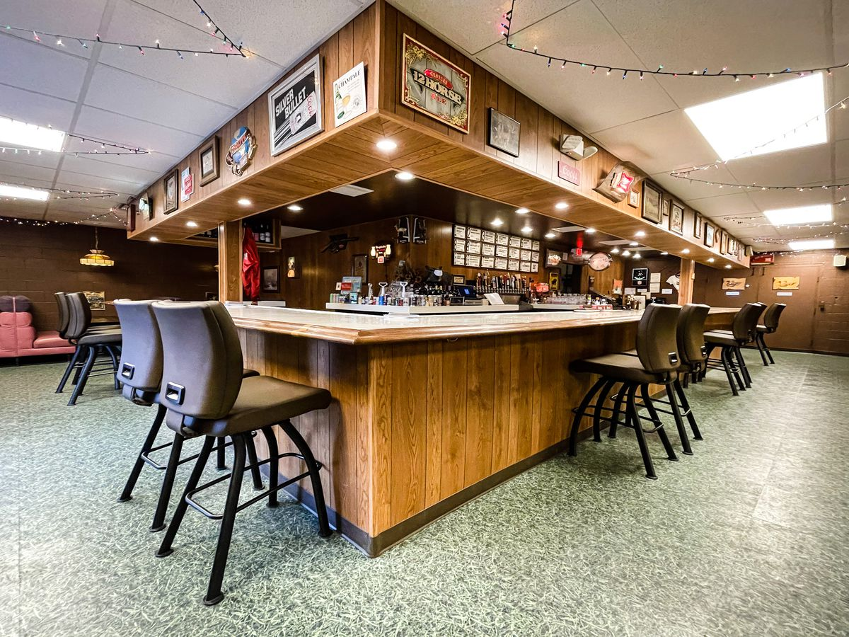 A wood square bar with leather high-top chairs around it.