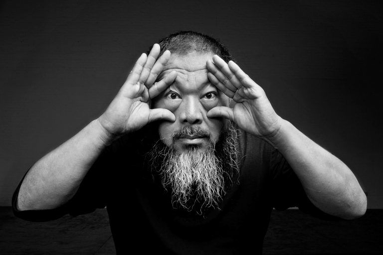 A black-and-white photo of Ai Weiwei where he holds both of his eyes open with two hands and stares into the camera.