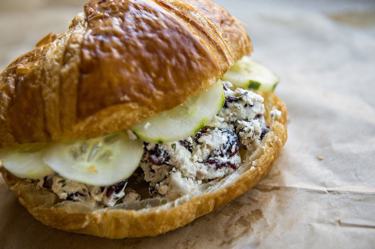 """Cafe and Velo's kitchen focuses on """"crandwiches"""" (croissant sandwiches), such as the Colnago with goat cheese, cranberries, cucumber, and walnuts."""