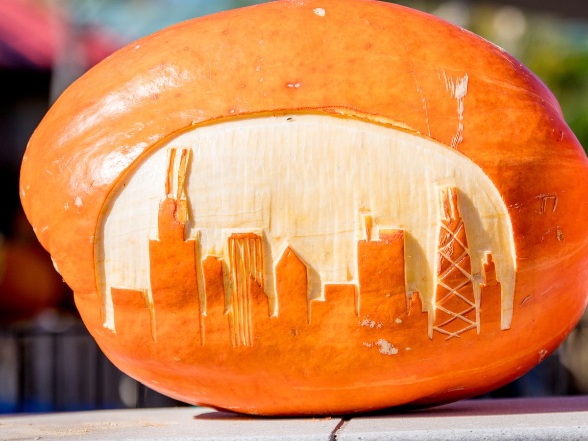 A pumpkin on its side carved with the shape of tall buildings resembling Chicago's skyline.