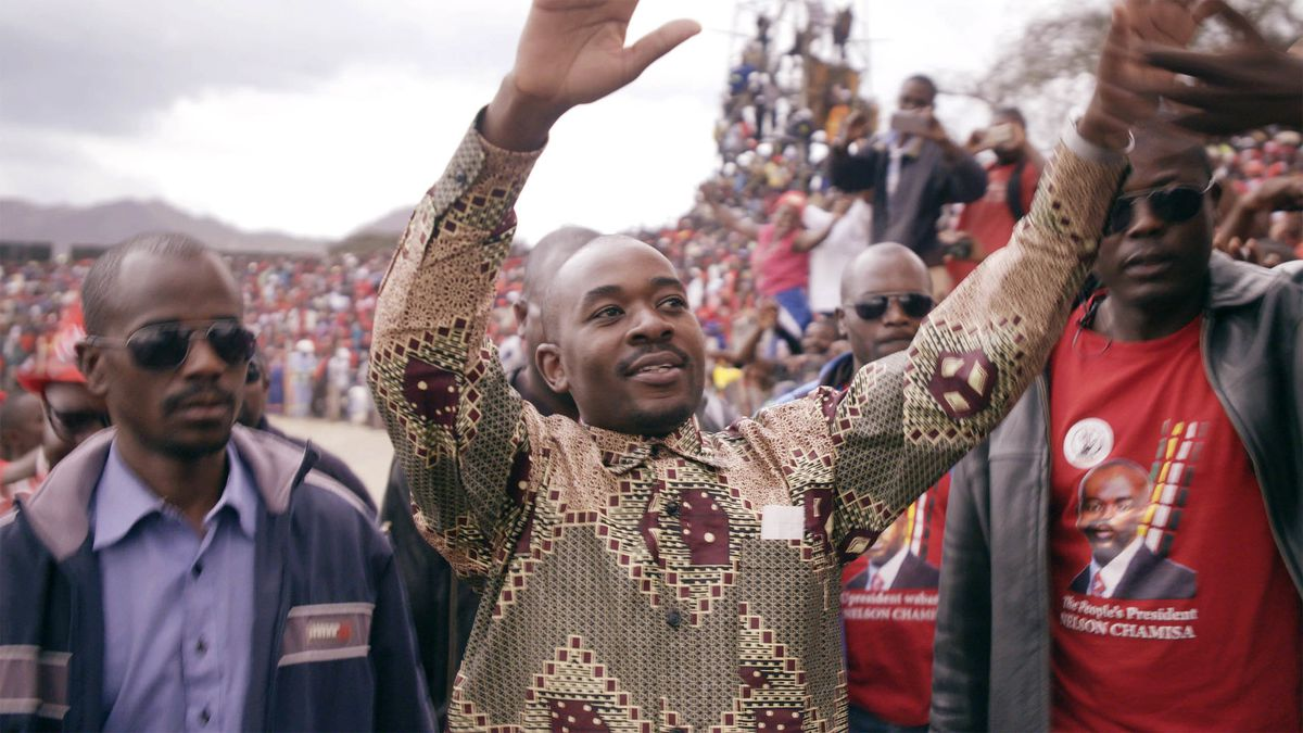 Zimbabwean presidential candidate Nelson Chamisa stands in the midst of a crowd, hands upraised to greet the people, flanked by bodyguards.