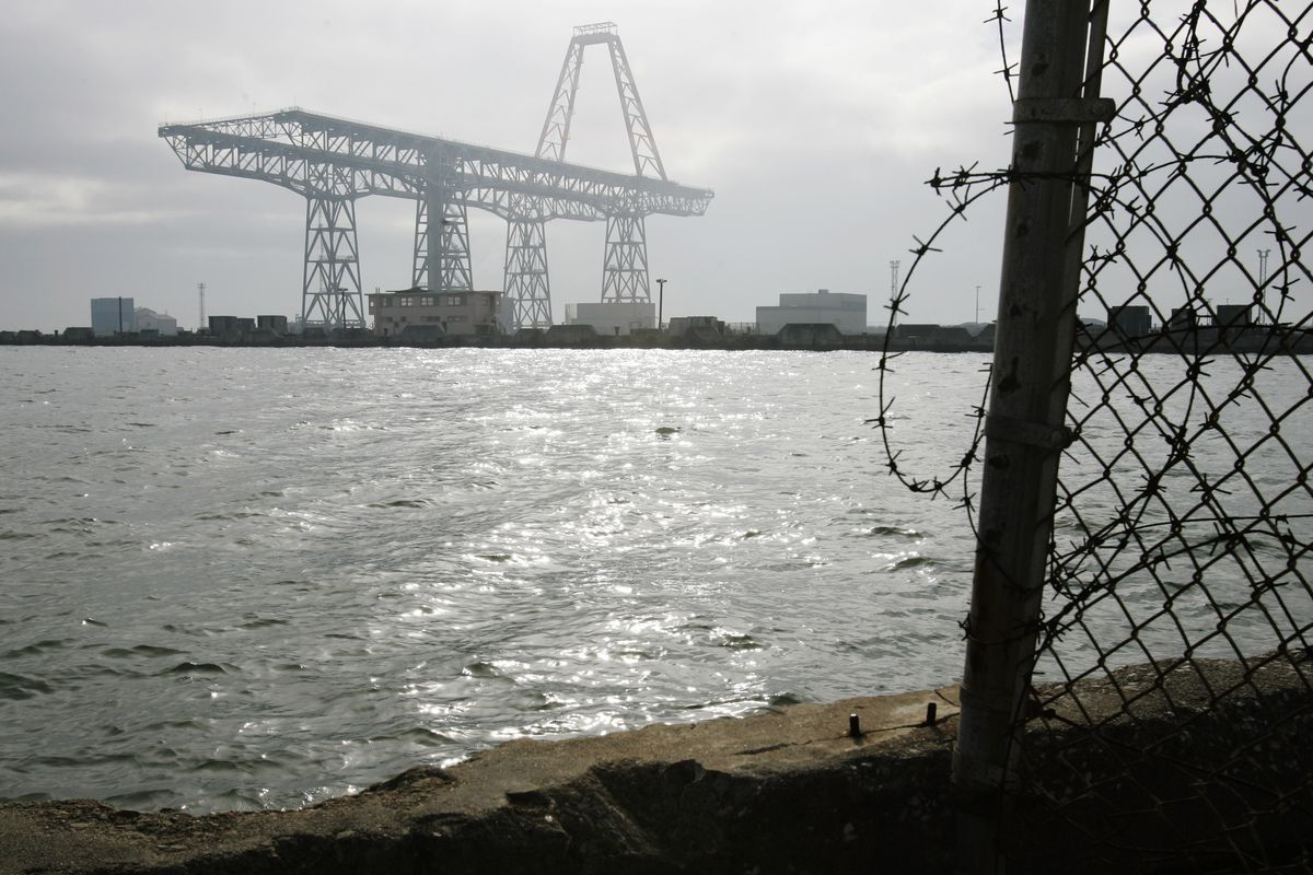A view of a large gantry crane just off the bay waters. A fence with barbed wire sits just to the right.