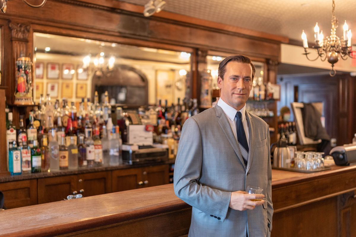 A wax figure resembling Jon Hamm stands at the bar of an American steakhouse in Brooklyn