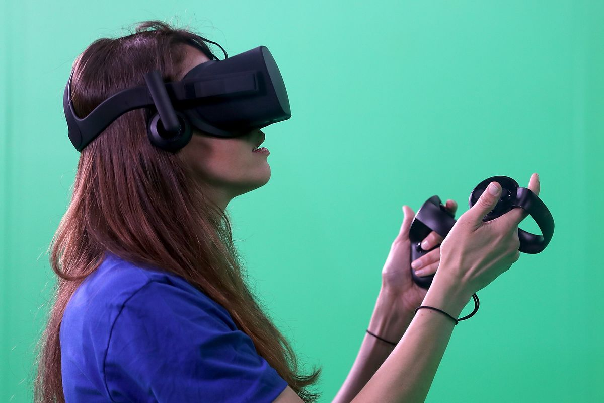 A woman wearing an Oculus Facebook virtual reality headset and holding controllers in her hands
