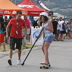 At top, a giant stand up paddleboard rides past vendors during the Open Air Demo Day for outdoor retailers on Wednesday at Jordanelle Reservoir.  Above, a Kahuna Big Stick vendor watches as a patron tries the Big Stick.