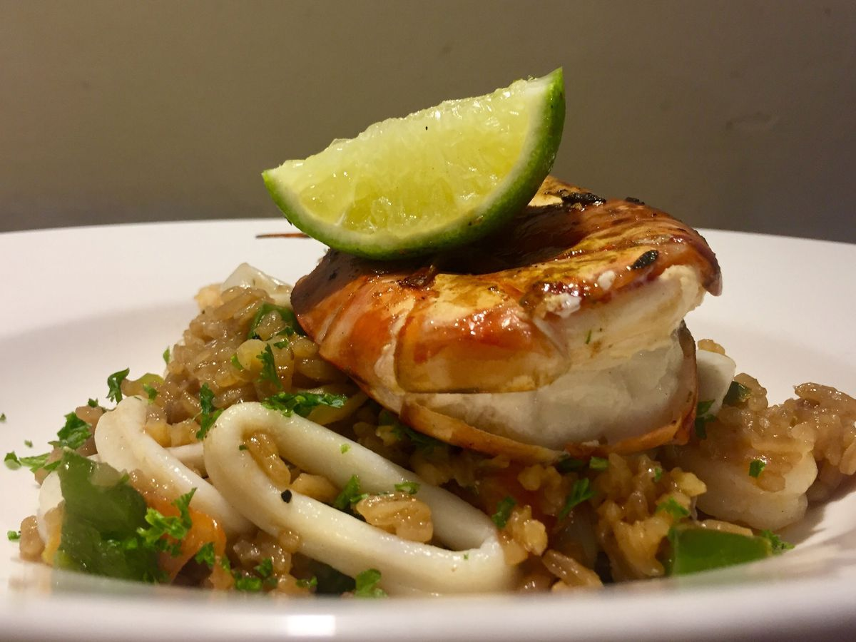 A large broiled shrimp sits on top of a mound of rice and rings of squid with a lime wedge resting on the very top