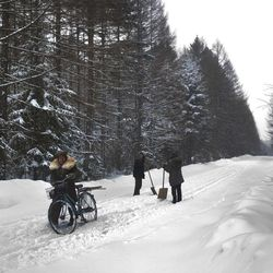 In this Monday, April 2, 2012 photo, people make their way along a snowy mountain road at the base of Mount Paektu, North Korea near a former secret camp that is said to have been the home of the late North Korean leader Kim Il Sung and the birthplace of his son and late leader Kim Jong Il.