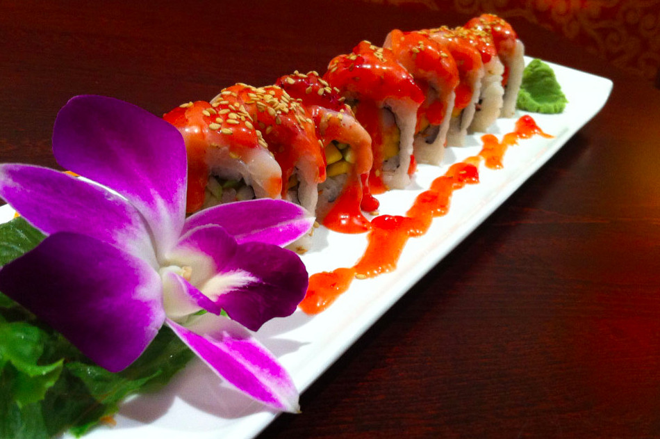 A sushi roll sits on a long white plate, garnished with a purple orchid