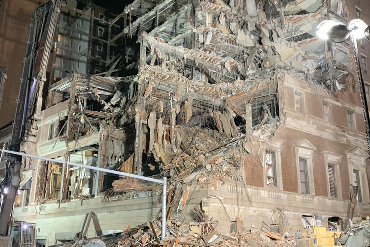 The partially demolished and caved-in exterior of a multi-story building.