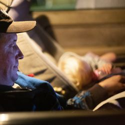 Matthew Branstetter watches a movie with daughter Julianna, 1, in one of the family's vehicles they currently live in at Lake Washington United Methodist Church in Kirkland, Wash., on Saturday, Oct. 12, 2019. Branstetter, his wife and three children have been using the Safe Parking program for the past several months, first becoming homeless in December 2018.