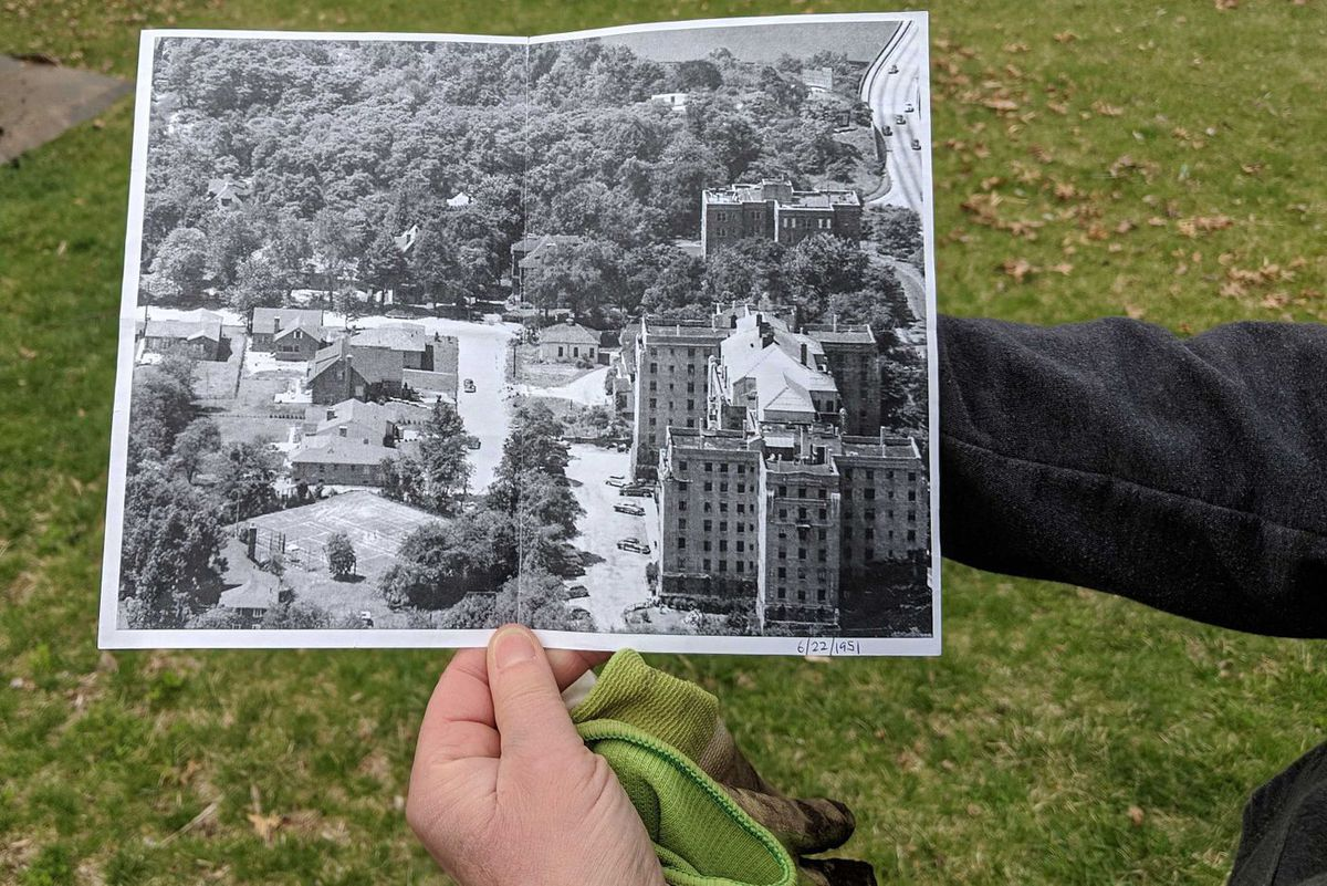 Guillemette Bowler, who lives next door to the Revolutionary War site, holds up a photo taken in the '50s when the vacant lot was a tennis club, April 11, 2019.