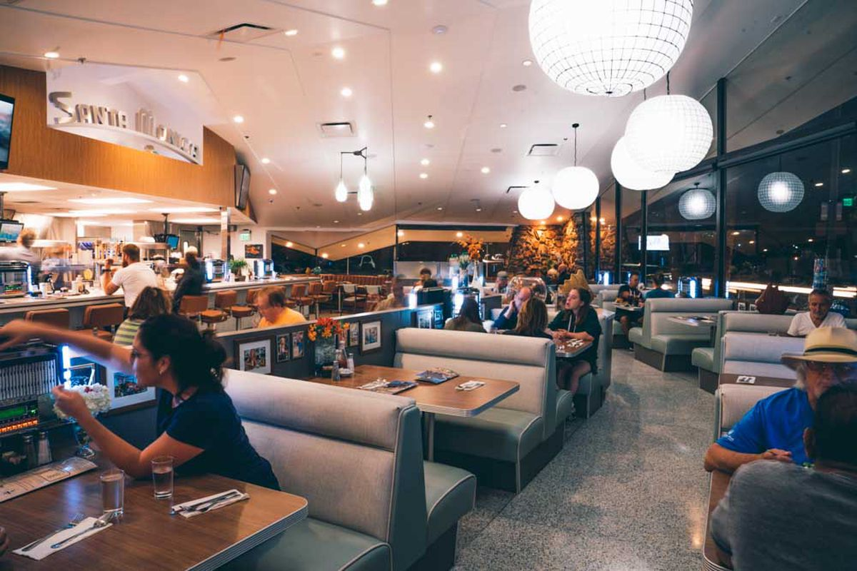 Diners sit inside of a vintage diner with wraparound glass and big booths.