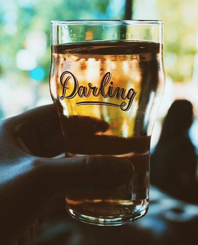 A glass of cider with Darling's logo on it.