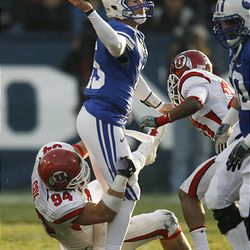 BYU quarterback Max Hall tries to avoid the sack of Utah defensive tackle Christian Cox (94) during during their game at LaVell Edwards Stadium in Provo Saturday. BYU won 26-23 in overtime.