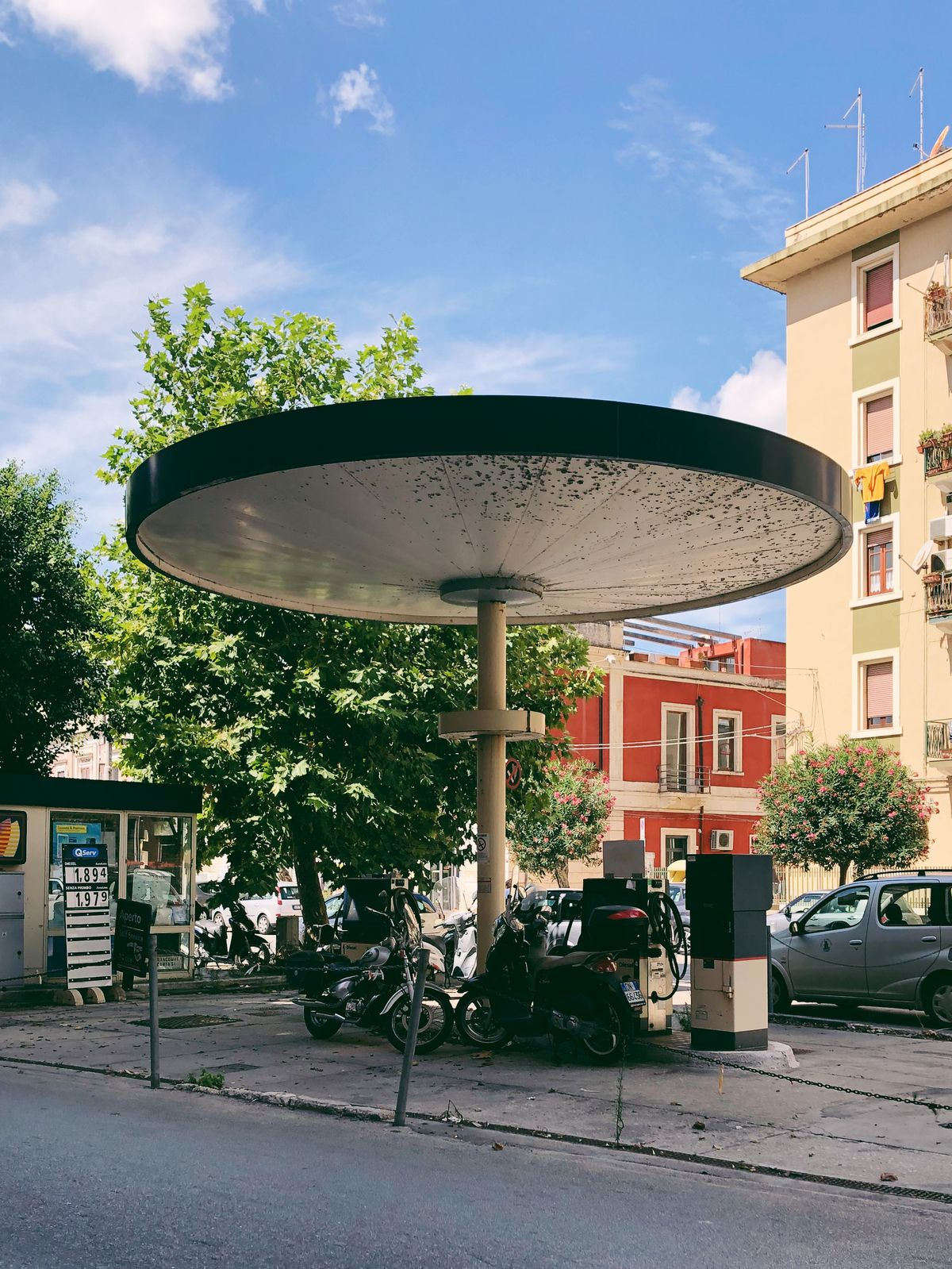 A round overhang provides shade to three motorcycles on the street.