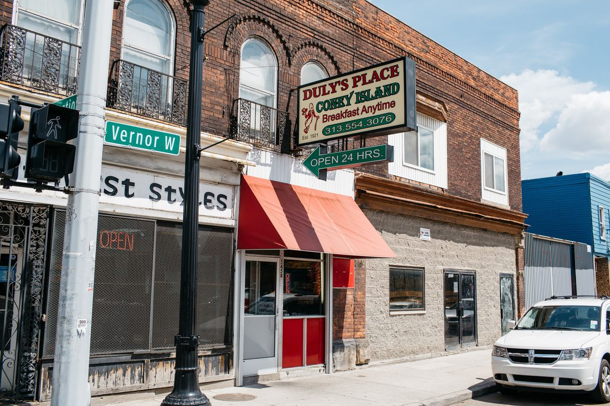 """The exterior of Duly's Place is shown in an old brick building next to barbershop Southwest Styles. Duly's has a green and red sign with an arrow pointing towards the restaurant that says """"24 Hours"""" and a red awning."""