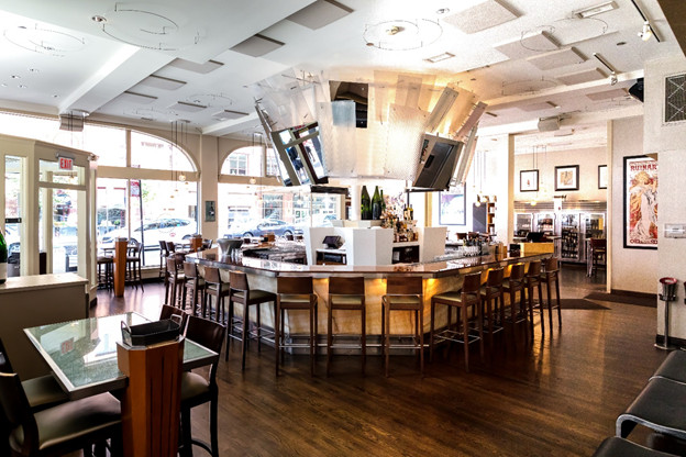 A central bar flanked by hightop tables.