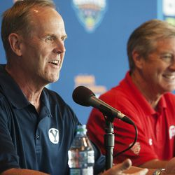 Tom Holmoe, athletic director at Brigham Young University and Chris Hill, athletic director at the University of Utah smile at a media event announcing the Zion's Bank Beehive Classic at the Vivint Arena in Salt Lake City, Thursday, July 21, 2016.