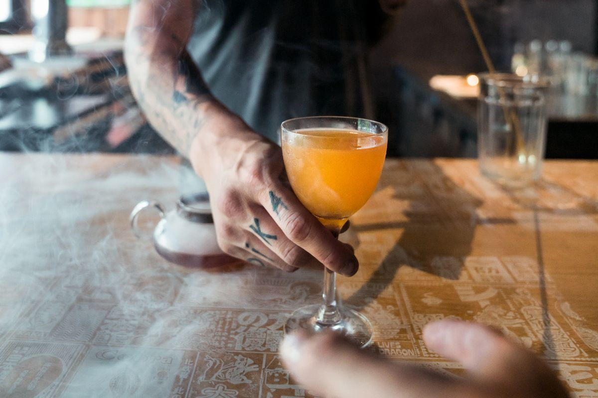 The tattooed arm of a bartender serves up an orange-colored cocktail on a wood bar to a waiting customer.