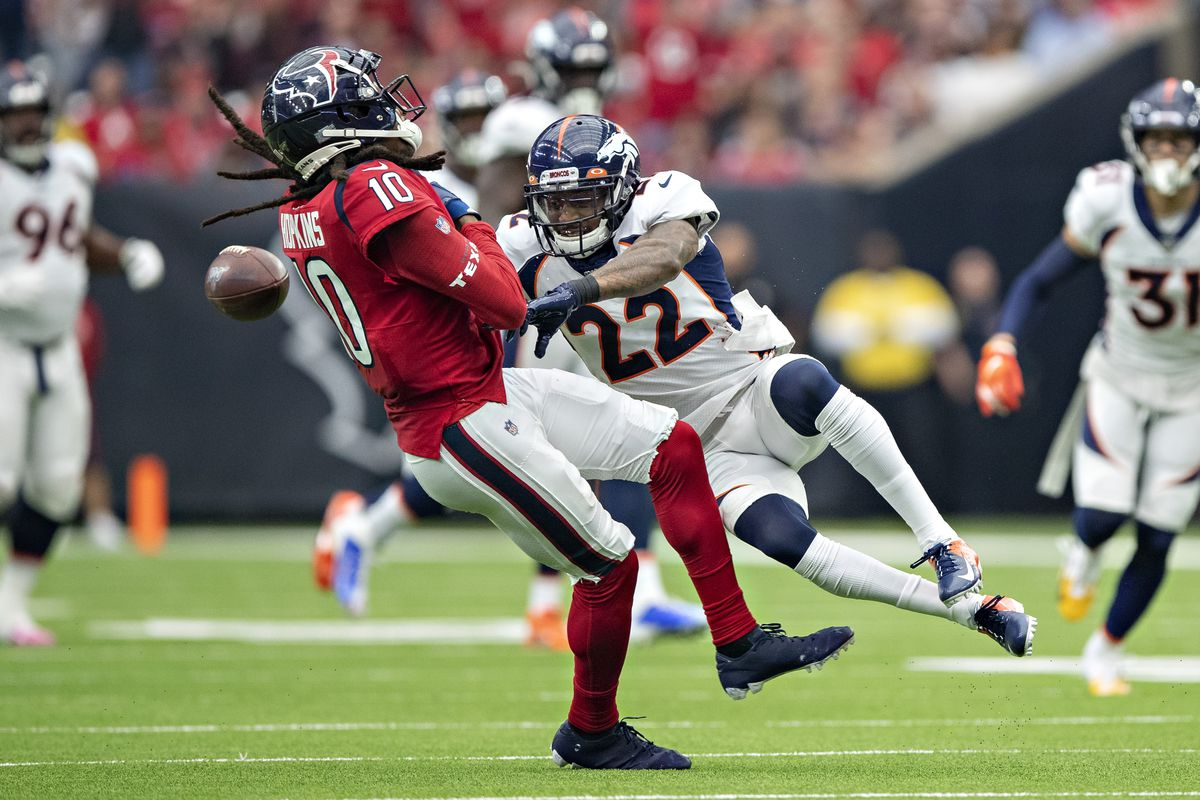 DeAndre Hopkins of the Houston Texans is hit after catching a pass and has the ball knocked Kareem Jackson of the Denver Broncos during the first half at NRG Stadium on December 8, 2019 in Houston, Texas.