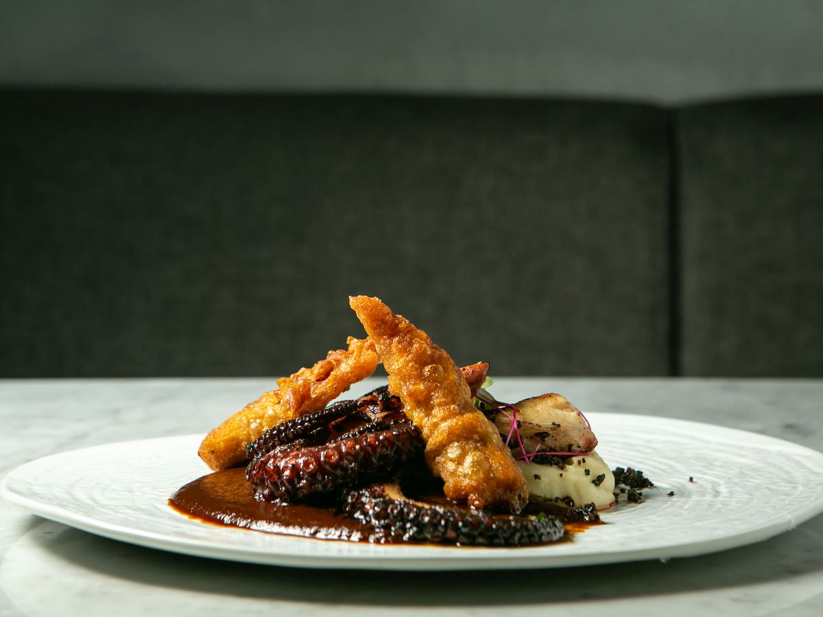 A side view of a plate with an octopus tentacle in brown sauce.
