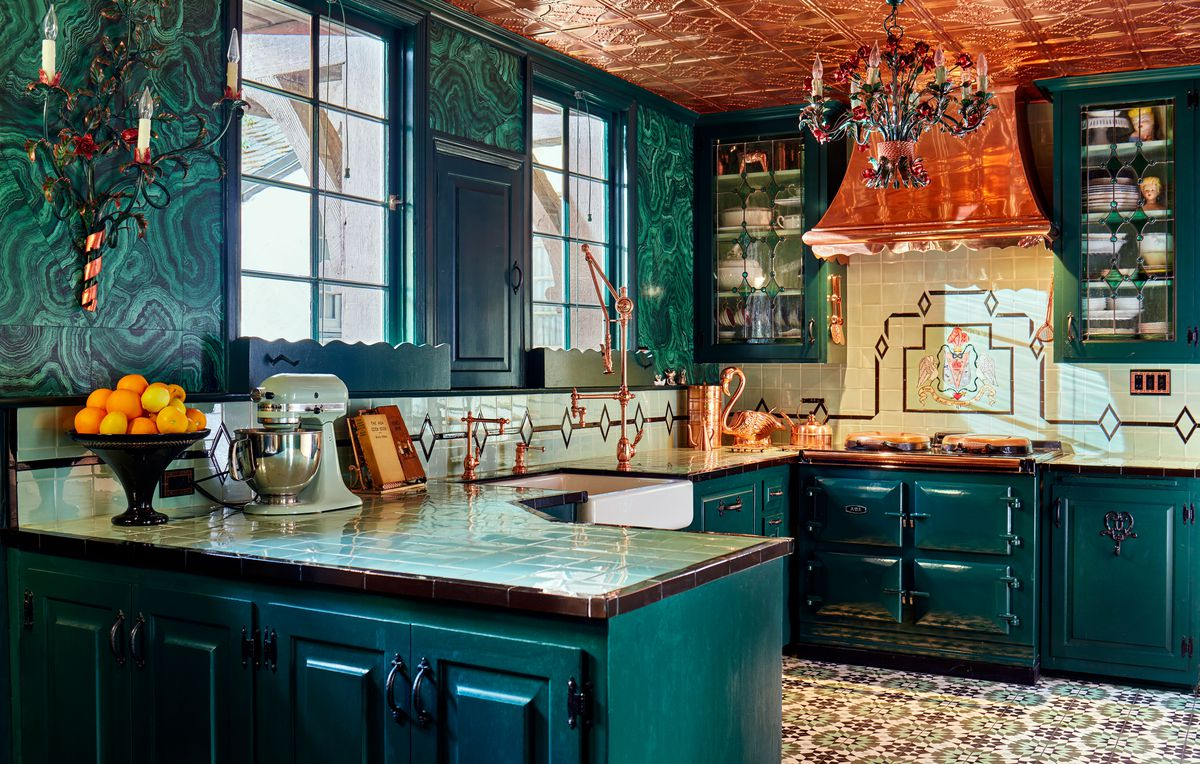 A teal and green kitchen with rose gold fixtures and rose gold metal tiles on the ceiling.