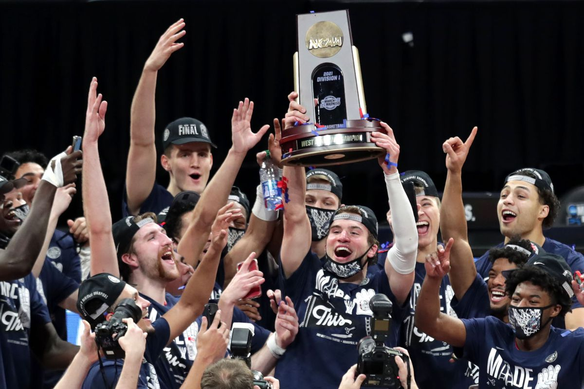 Gonzaga players celebrate at center court with their trophy after defeating USC during the Elite Eight round of the 2021 NCAA Tournament on Tuesday, March 30, 2021, at Lucas Oil Stadium in Indianapolis, Ind.
