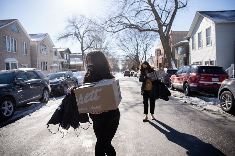 White Sox staffers carry donated food to Chicago Fire Department firefighters Thursday at Engine 29 in Bridgeport. White Sox pitcher Liam Hendriks and his wife Kristi donated lunch from local restaurants to about half a dozen firefighters.