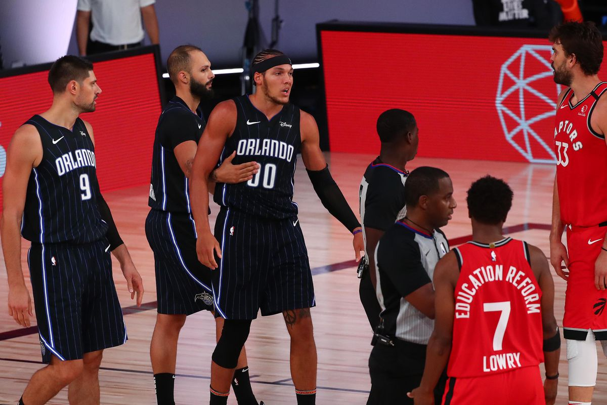 Aaron Gordon of the Orlando Magic is held back by Evan Fournier after being fouled by Kyle Lowry  of the Toronto Raptors in the second half at Visa Athletic Center at ESPN Wide World Of Sports Complex on August 5, 2020 in Lake Buena Vista, Florida.