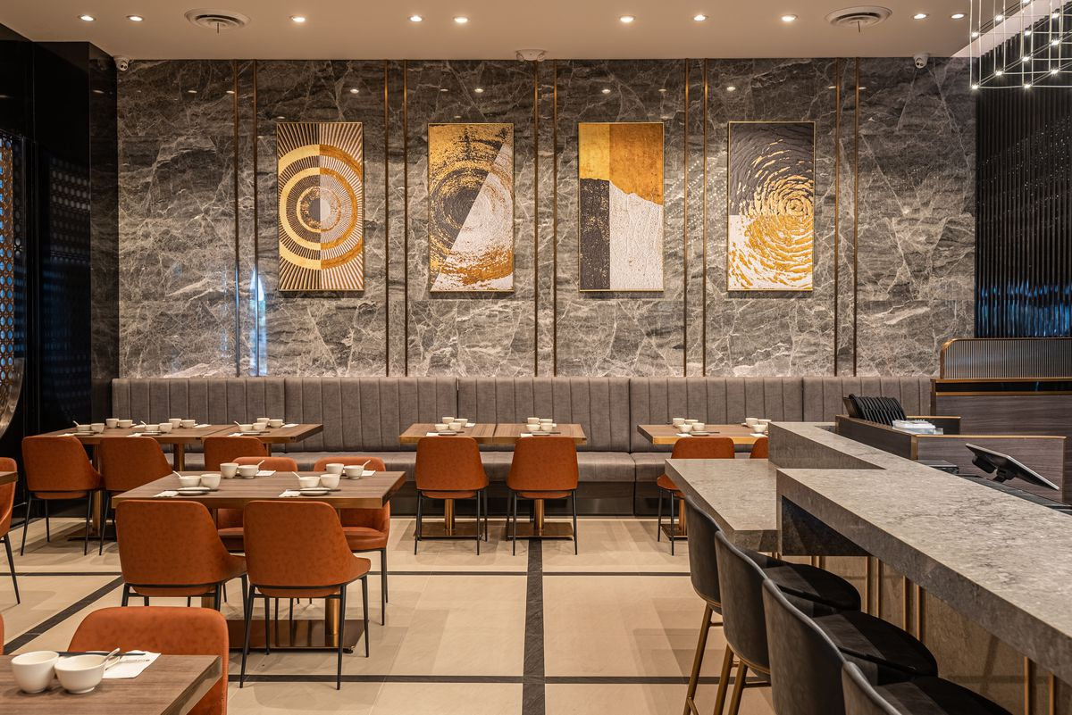 Grey and gold touches inside of an upscale new dumpling restaurant.