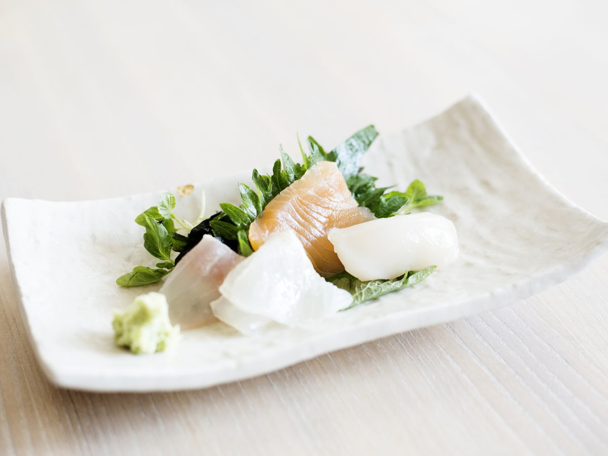 Several pieces of white and pink sashimi on a white plate with green foliage garnish