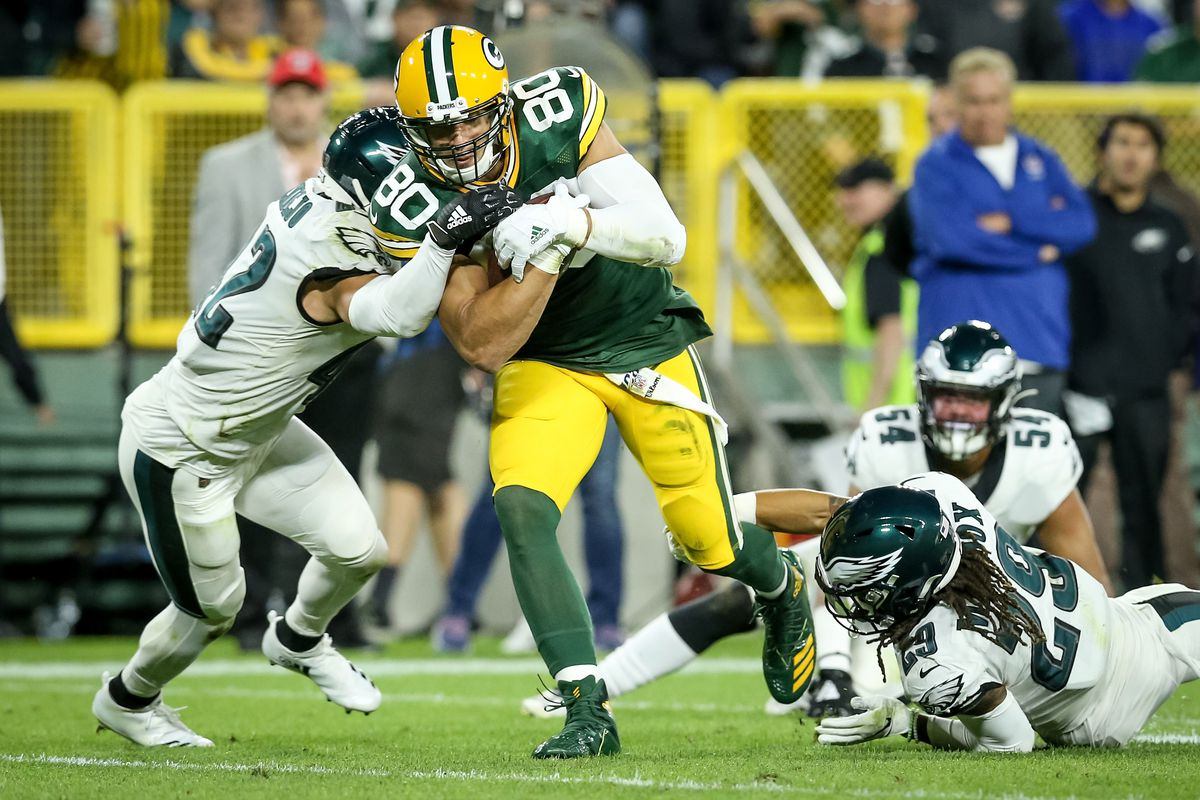 Jimmy Graham of the Green Bay Packers runs with the ball while being tackled by Andrew Sendejo of the Philadelphia Eagles in the third quarter at Lambeau Field on September 26, 2019 in Green Bay, Wisconsin.