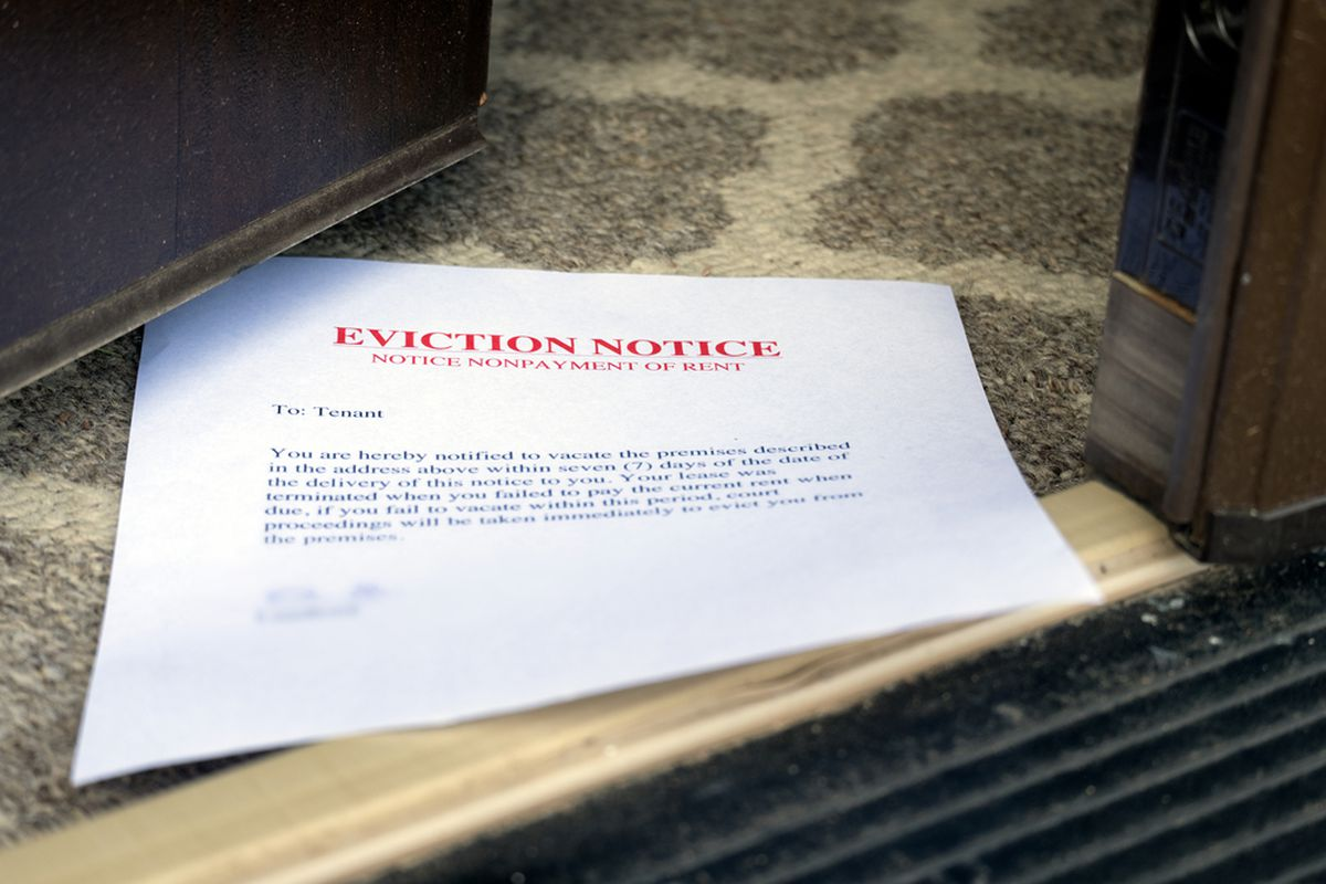 An eviction notice slipped underneath an apartment building door.
