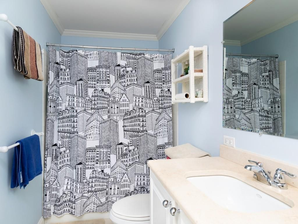 A small bathroom with the curtain pulled across the shower.