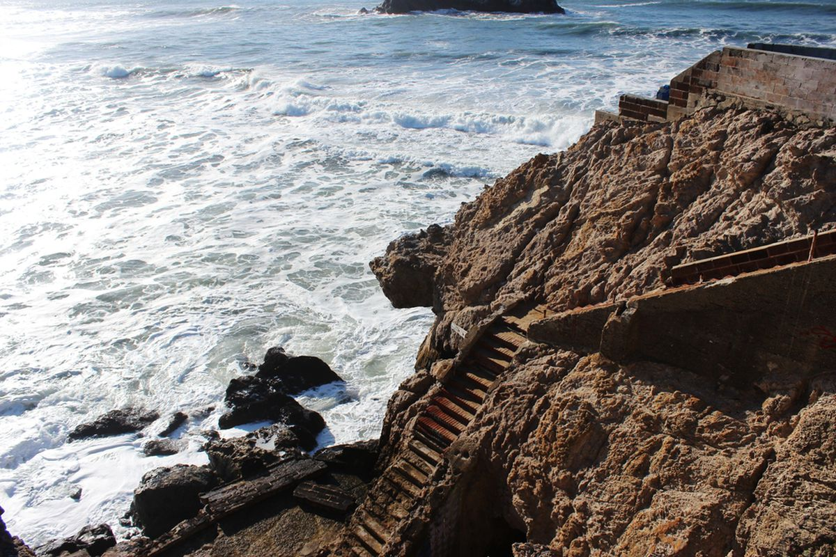 Steps leading down from the ruins of the Sutro Baths to a turgid ocean at Ocean Beach.