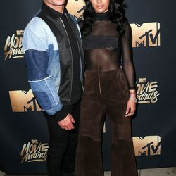 Zac Efron wears a denim jacket while his girlfriend Sami Miro wears a sheer top and flared trousers.