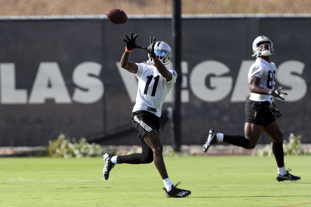 Henry Ruggs III #11 of the Las Vegas Raiders catches a pass during training camp at the Las Vegas Raiders Headquarters/Intermountain Healthcare Performance Center on July 29, 2021 in Henderson, Nevada. Bryan Edwards #89 is at right.