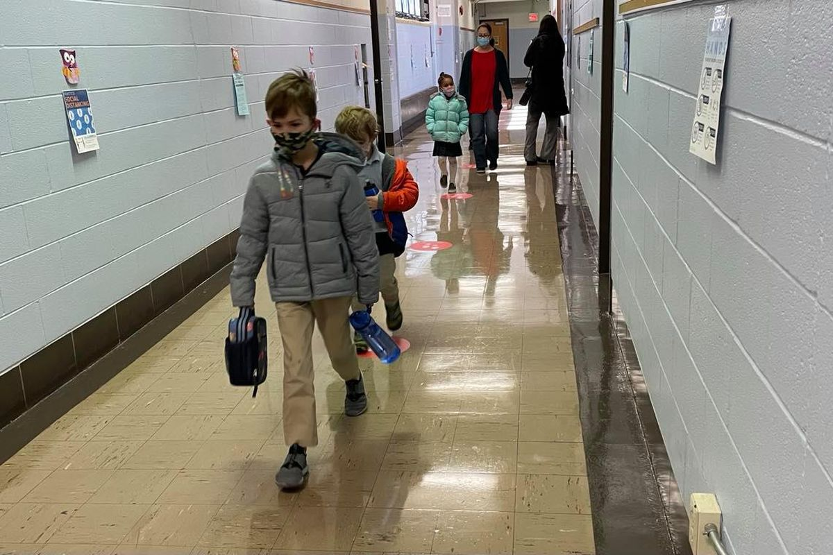 Wearing masks, kindergarten students walk back to their classroom after taking a restroom break at Chester Arthur Elementary School in South Philadelphia.