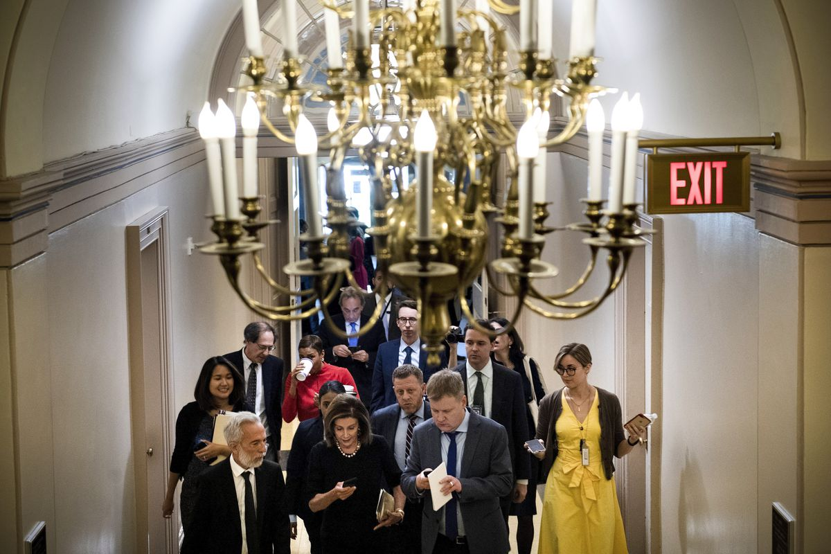 Speaker of the House Nancy Pelosi walks from a meeting with House Democrats. The photograph has a huge chandelier in the foreground.