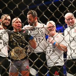 Newly crowned UFC middleweight champion Georges St-Pierre, along with his team, poses for photographs inside the Octagon.
