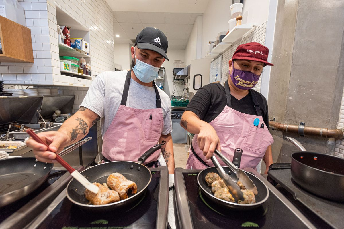Two workers in pink aprons turn meatballs inside of frying pans at a corporate kitchen.