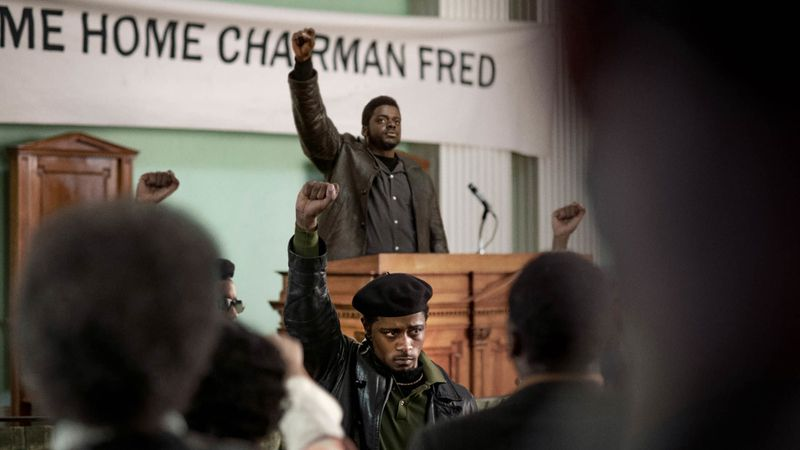"""Fred Hampton stands at a podium in front of a banner reading """"Welcome Back Chairman Fred,"""" with William O'Neal in front of him. Both raise their fists."""