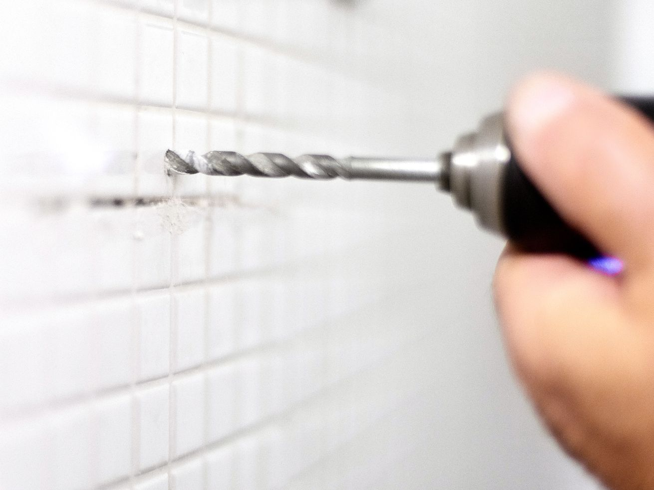 Drilling hole in tile in shower.