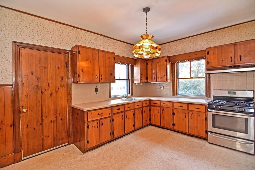 An empty kitchen with a lot of older, lacquered cabinetry and counters meeting at a right angle.