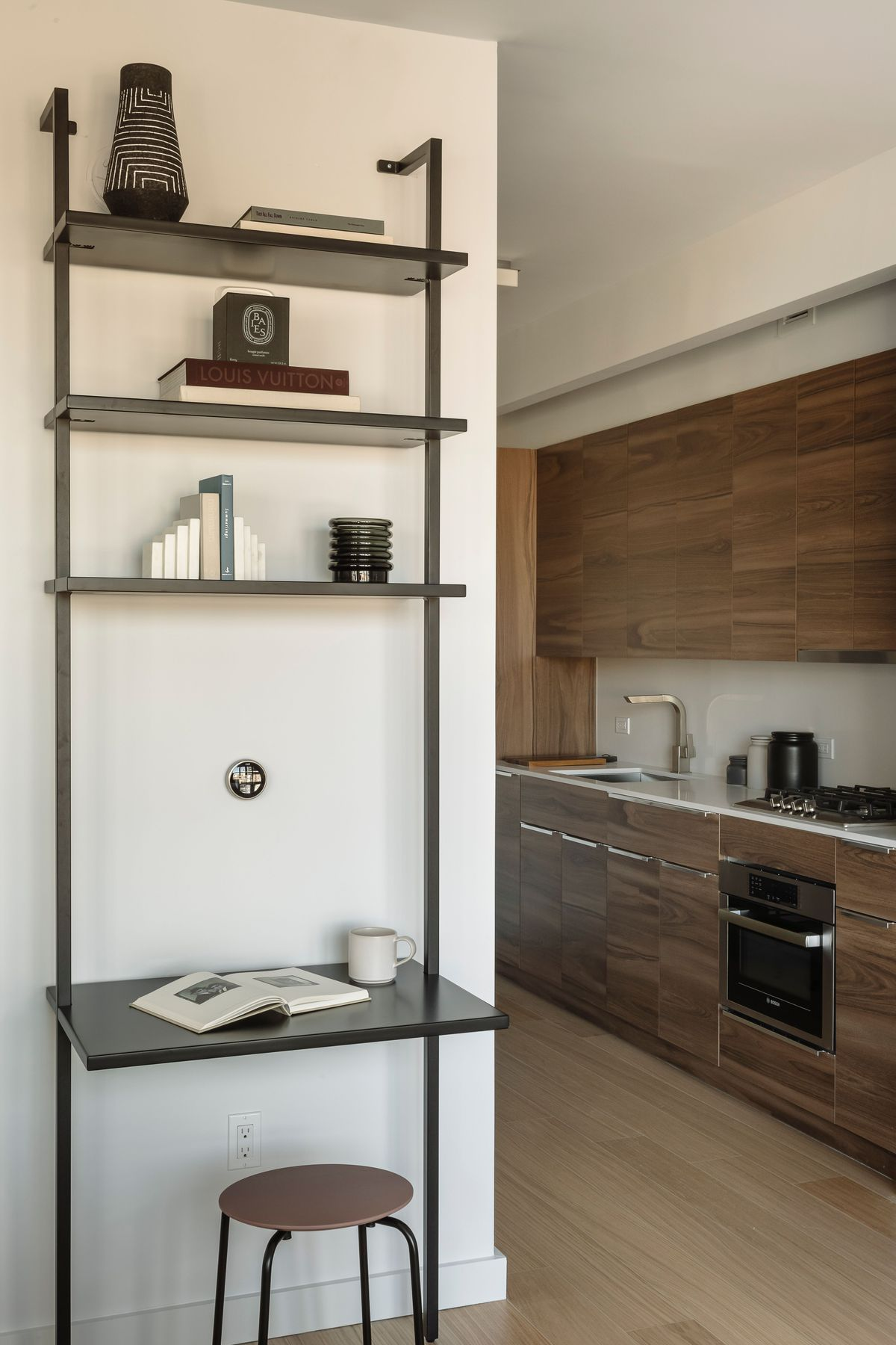 An area with a bookshelf and a kitchen behind it.