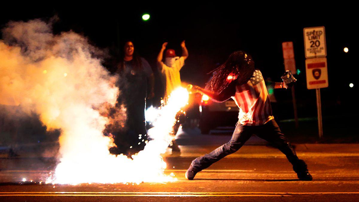 Ferguson protester throws back tear gas.