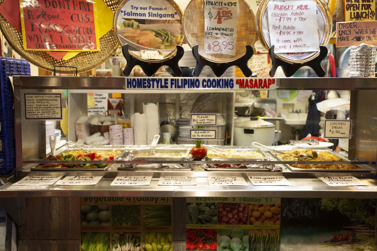The counter at Oriental Mart at Pike Place, with various hand-drawn signs displayed.