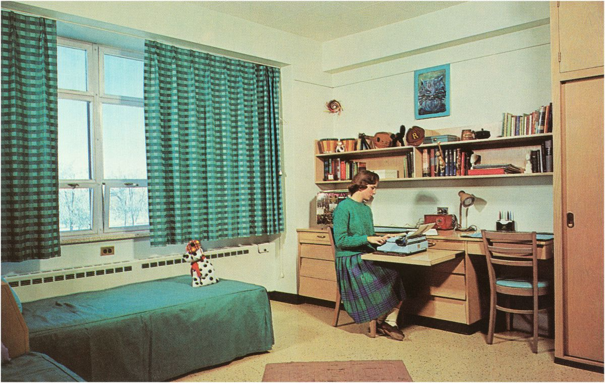 Vintage photograph of a of college student in sweater and skirt, sitting at a built-in desk, working at a typewriter in her color-coordinated green dorm room, 1950s.