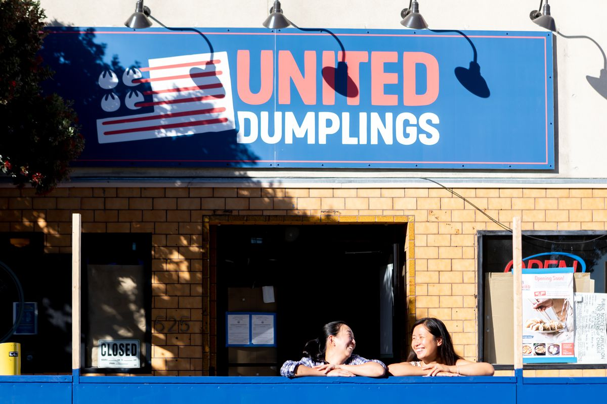 """Two women stand in an outdoor dining area, laughing, in from of the """"United Dumplings"""" sign  (with a U.S. flag-inspired logo) above the restaurant"""